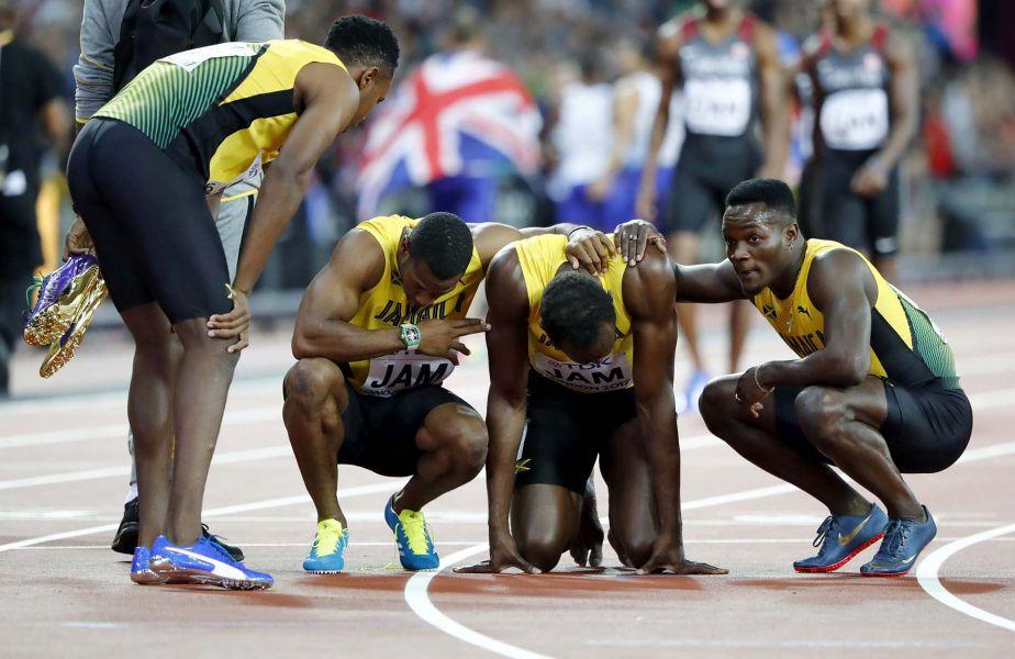 Los compañeros del equipo de posta 4 x 100 de Jamaica, consuelan a Usain Bolt, que en su última noche, una lesión lo dejó sin el podio.