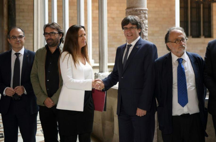 El presidente de Cataluña, Carles Puigdemont, saluda a la presidenta de la comisión independiente para la mediación, María Eugenia Gay. (Foto AFP).