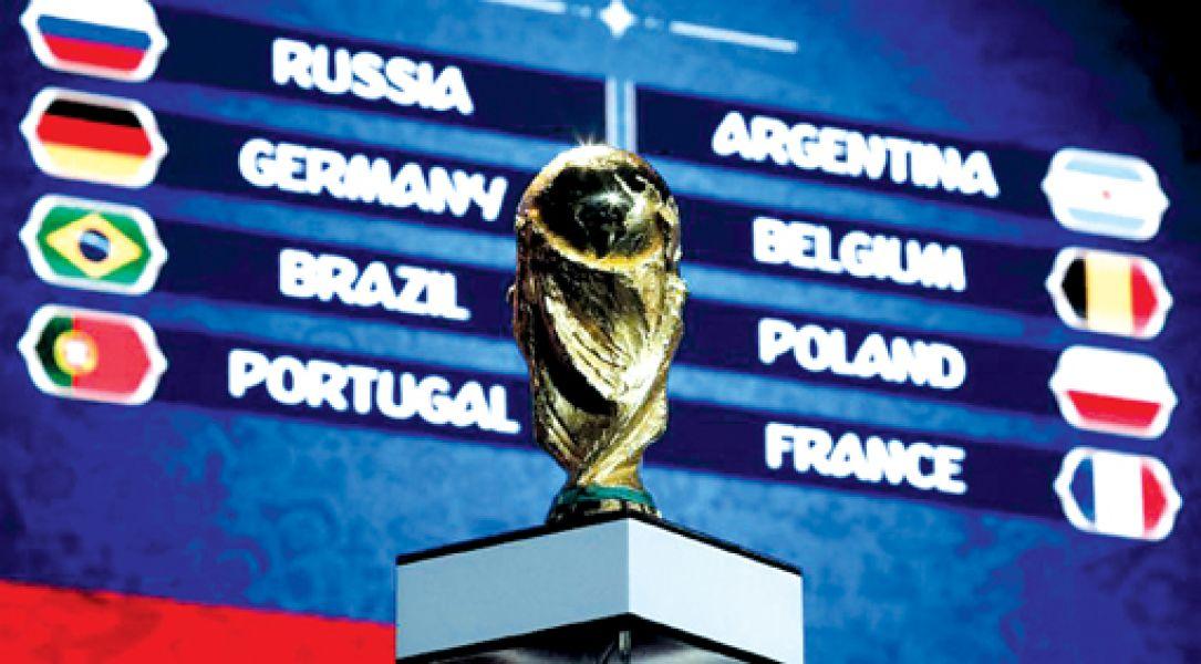 La Copa del Mundo, en el ensayo del sorteo que se realizará esta tarde. De fondo, los equipos cabeza de serie.