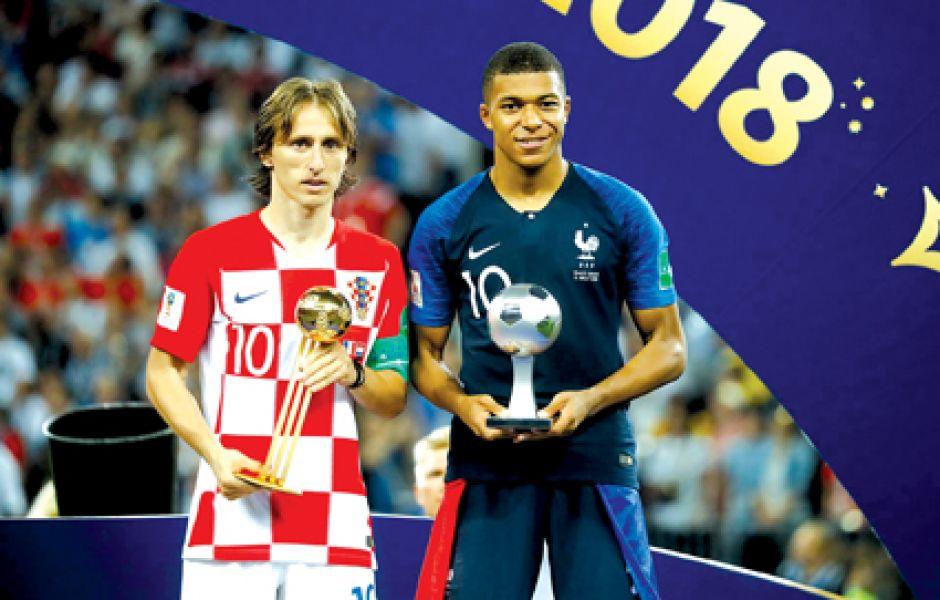 Presente y futuro. Luka Modric y Kylian Mbappé con los trofeos recibidos.