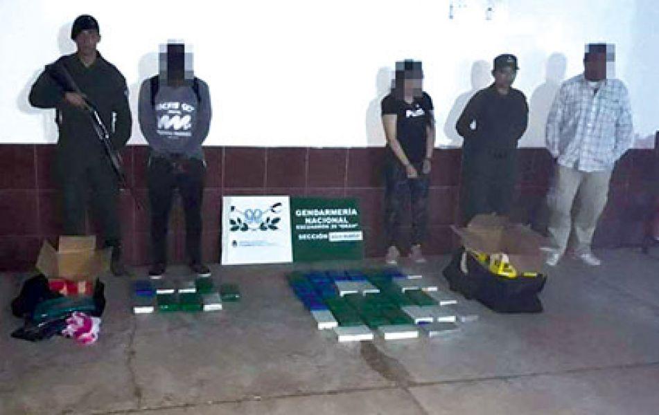 Al medio del grupo está la pareja detenida en Aguas Blancas, junto a la droga secuestrada por los gendarmes.