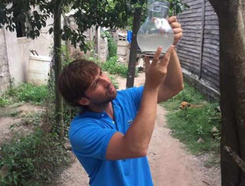 El diputado Emanuel Sierra muestra en la jarra el agua color marrón que sale de las canillas en Metán.