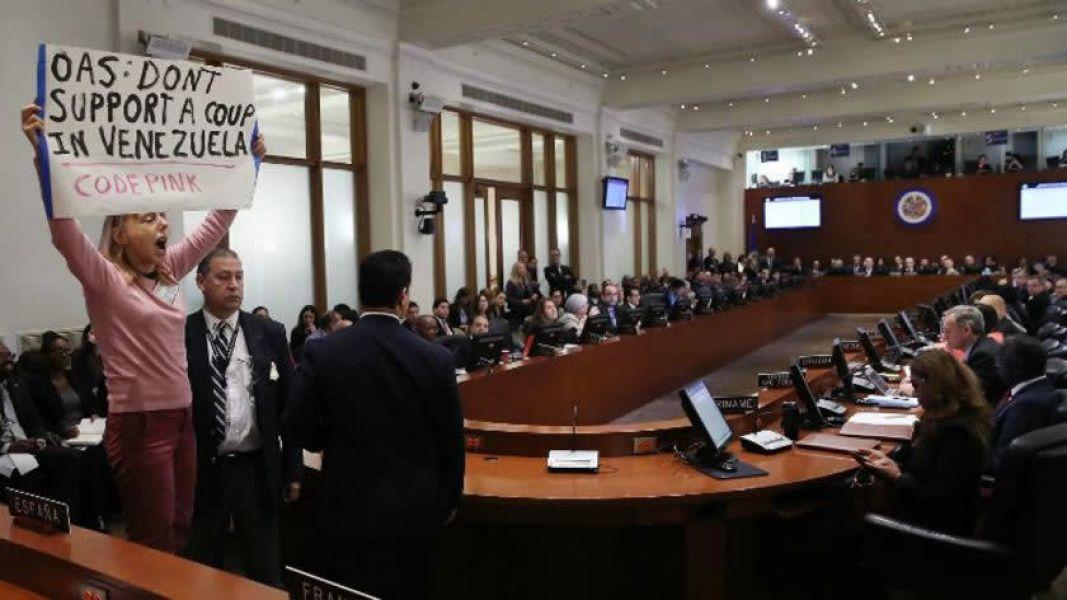 """Una activista irrumpe en la sesión de la OEA con el cartel: """"OEA no apoyes un golpe de Estado en Venezuela""""."""