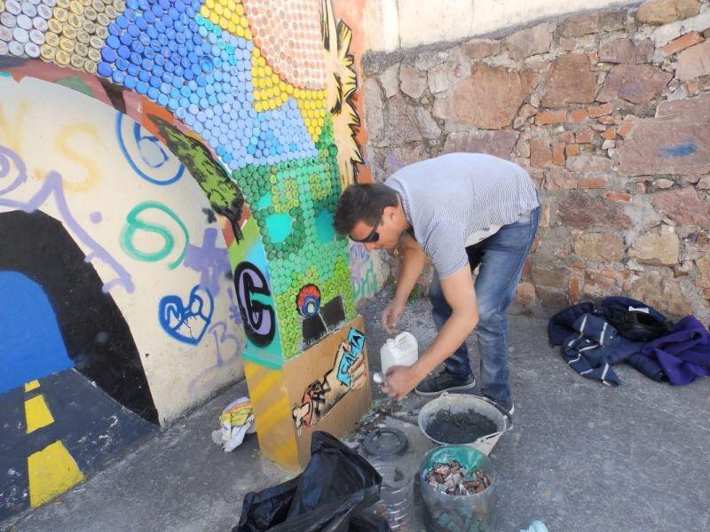 Carlos Robles, es el artista que trabaja el mural ecológico realizado casi totalmente con tapitas plásticas en desuso.