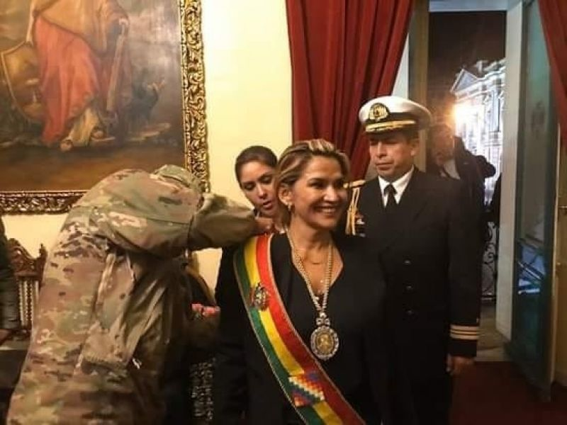 Jeanine Añez, recibe la banda presidencial de manos de un militar, sin quórum en el Congreso boliviano.