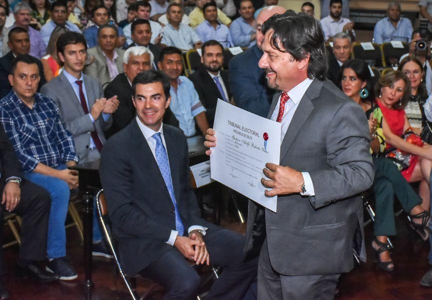 Gustavo Sáenz exhibe el diploma que lo proclama como gobernador electo de la Provincia. De la ceremonia participó el gobernador Urtubey.