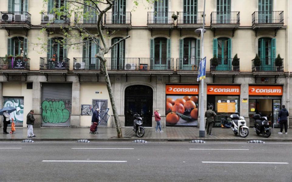 Una fila espaciada de españoles para comprar en un supermercado de Barcelona.